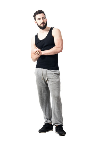 man shirt: Bearded muscular athlete with clasped hands looking up pensive. Toned desaturated full body length portrait isolated on white studio background.