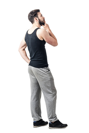 man profile: Side view of man in tank top and sweatpants looking up with hand on chin. Toned desaturated full body length portrait isolated on white studio background.
