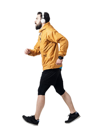 brisk: Side view of athlete jogging with headphones wearing jacket. Toned desaturated full body length portrait isolated on white studio background.