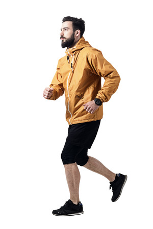 running pants: Side view of athletic man jogging in jacket looking up. Toned desaturated full body length portrait isolated on white studio background. Stock Photo