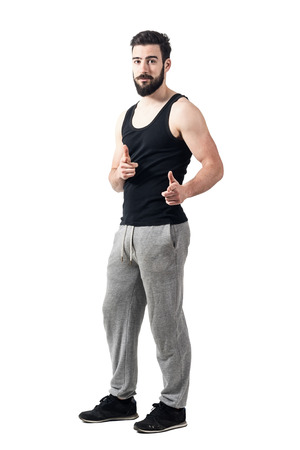 fingers on top: Young athlete in tank top pointing fingers at camera. Toned desaturated full body length portrait isolated on white studio background. Stock Photo