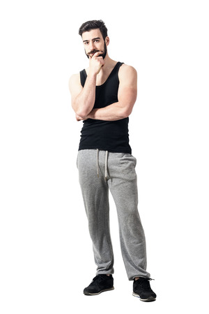 Muscular young man wearing black undershirt with hand on chin. Toned desaturated full body length portrait isolated on white studio background. Stock Photo