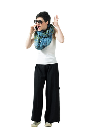 woman shouting: Angry upset casual woman yelling at mobile phone. Full body length portrait isolated over white studio background.