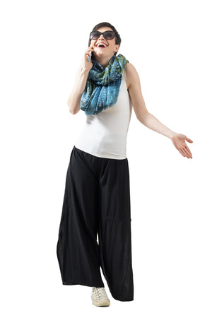 Relaxed casual woman on the phone laughing looking up. Full body length portrait isolated over white studio background.