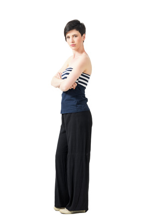 off shoulder: Confident serious short hair woman with crossed arms looking at camera. Full body length portrait isolated over white studio background.