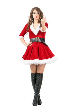 Cute angry female Santa giving middle finger obscene gesture at camera. Full body length portrait isolated over white studio background.