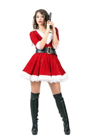Gefährliche femme fatale als Weihnachtsmann-Frau hält Pistole gekleidet. Ganzkörper-Länge Portrait über weißem Hintergrund Studio isoliert. Standard-Bild