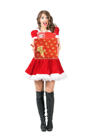 mrs santa claus: Excited amazed mrs. Santa Claus giving many gifts looking at camera. Full body length portrait isolated over white studio background.