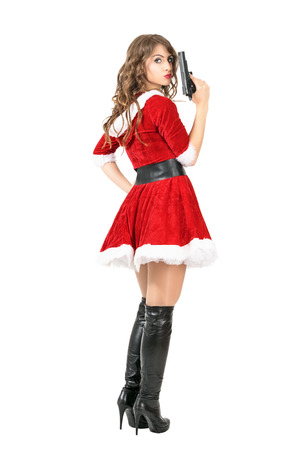 Rear view of dangerous femme fatale in Christmas costume holding gun turning head at camera. Full body length portrait isolated over white studio background. Stock Photo