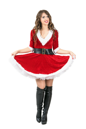 mrs santa claus: Beautiful playful Santa Claus woman lifting skirt with petticoat posing at camera. Full body length portrait isolated over white studio background.