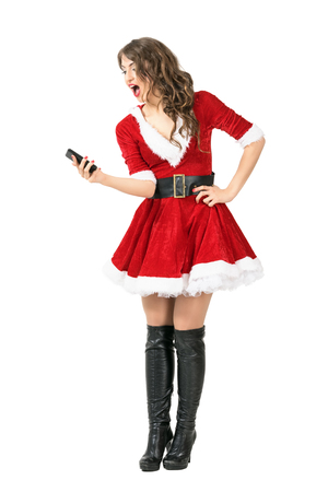 mrs santa claus: Excited Santa Claus woman taking selfie with smart phone. Full body length portrait isolated over white studio background. Stock Photo