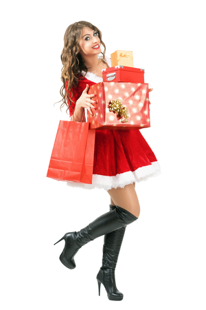 mrs santa claus: Happy excited beautiful Santa Claus woman carrying lots of Christmas gifts walking. Full body length portrait isolated over white studio background.