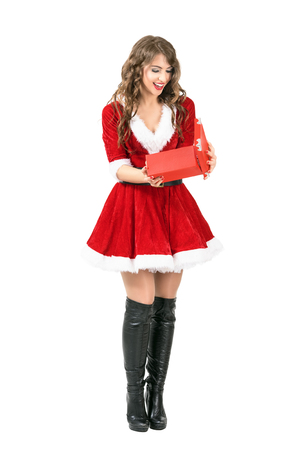 Happy excited Santa Claus woman opening Christmas gift with mouth open. Full body length portrait isolated over white studio background.