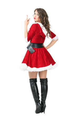 flipping: Rear view of rude female Santa Claus flipping middle finger at camera. Full body length portrait isolated over white studio background. Stock Photo
