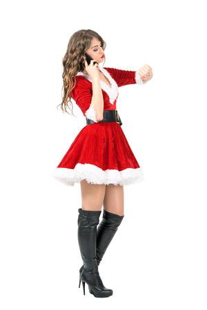 señora: Vista lateral de la señora de Navidad. Noel en el momento de la comprobación de teléfono. la longitud del cuerpo Retrato completo aislado sobre fondo blanco del estudio. Foto de archivo