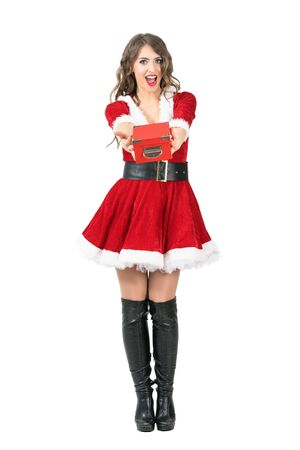 Front view of amazed Santa Claus woman giving Christmas gift looking at camera. Full body length portrait isolated over white studio background. Stock Photo