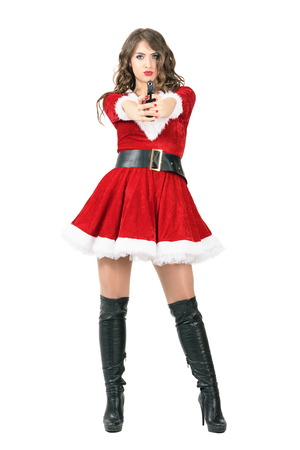 Femme fatale spy dressed as Santa Claus woman pointing pistol at camera. Full body length portrait isolated over white studio background.