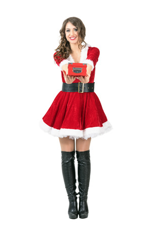 mrs santa claus: Beautiful happy female Santa Claus giving red gift box to you. Full body length portrait isolated over white studio background.