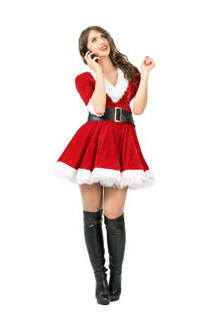 Happy Christmas Santa Claus woman talking on the mobile phone looking up. Full body length portrait isolated over white studio background.