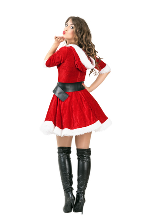 mrs santa claus: Back view of sexy attractive young female Santa Claus blowing a kiss at camera. Full body length portrait isolated over white studio background.