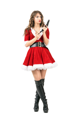 reloading: Female spy disguised as Santa Claus reloading handgun looking at camera. Full body length portrait isolated over white studio background. Stock Photo
