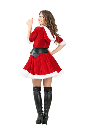 mrs santa claus: Rear view of sexy female Santa Claus showing thumbs up turning to camera. Full body length portrait isolated over white studio background. Stock Photo