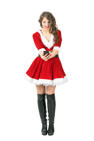 Front view of smiling beautiful Santa Woman taking selfie with smartphone. Full body length portrait isolated over white studio background. Stock Photo