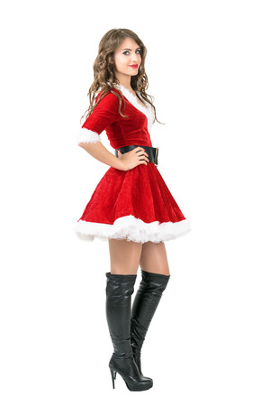 Side view of lovely Santa girl in Christmas dress posing with hands on hips. Full body length portrait isolated over white studio background Stock Photo