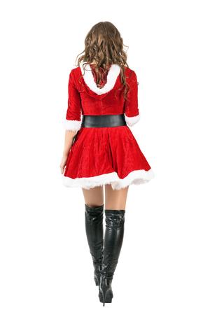 femme brune sexy: Vue arrière de la femme du Père Noël en robe rouge de Noël va. longueur complet du corps portrait isolé sur fond blanc studio