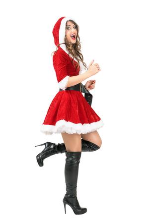 botas de navidad: Vista lateral de emocionados alegre mujer de santa claus en ejecución. longitud de cuerpo completo retrato aislado sobre fondo blanco estudio