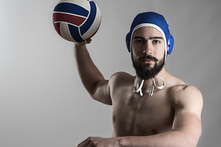water polo: Profesional jugador de waterpolo tiro pelota mirando a la cámara sobre fondo gris de estudio Foto de archivo