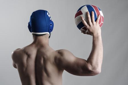 waterpolo: Vista posterior de la celebración de jugador de waterpolo muscular y disparar pelota. retrato descarnado desaturado sobre fondo gris.