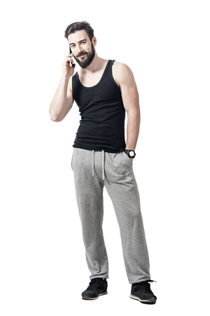 Young fit bearded man in sportswear smiling and talking on the cell phone. Full body length portrait isolated over white studio background