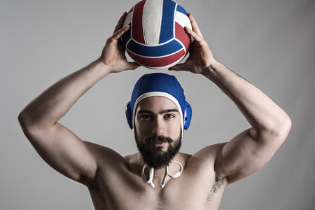 waterpolo: Happy professional water polo player holding ball over his head looking at camera over gray studio background Stock Photo