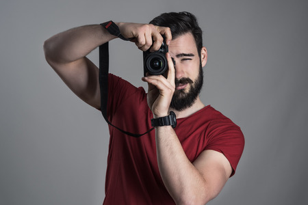 desaturated: Desaturated portrait of photographer taking photo with dslr camera holding vertically over dark gray studio background.