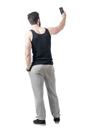 Rear view of muscular gym man taking selfie photo with mobile phone. Full body length portrait isolated over white studio background