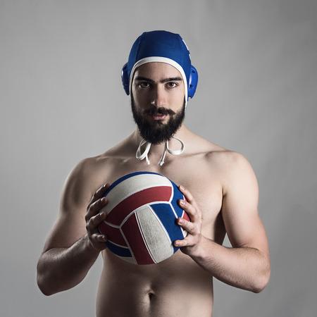waterpolo: Retrato confidente orgulloso de profesionales jugador de waterpolo que sostiene la bola mirando a la cámara.