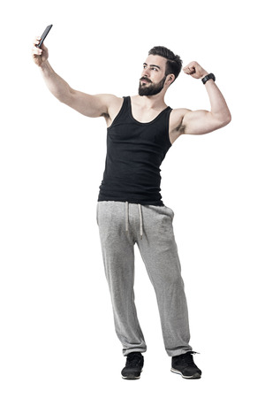 Fit young man flexing bicep arm muscle while taking selfie photo with mobile phone. Full body length portrait isolated over white studio background Stock Photo