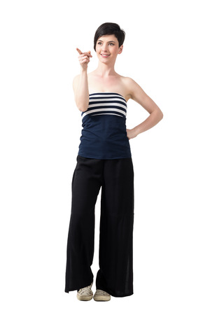 Pretty fashionable short hair woman pointing away and smiling. Full body length portrait isolated over white studio background. Stock Photo