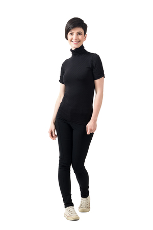 Young trendy slim short hair woman in black turtleneck t-shirt and pants smiling at camera. Full body length portrait isolated over white studio background.