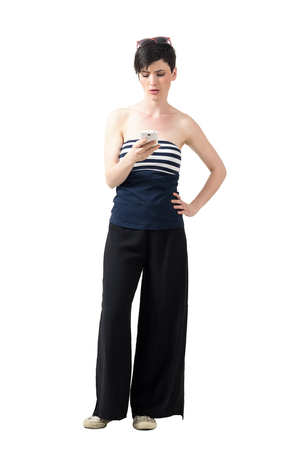 off shoulder: Frustrated young trendy woman in wide-leg pants typing message on cellphone. Full body length portrait isolated over white studio background.