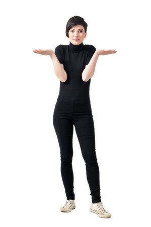 turtleneck: Funny confused clueless young woman in black turtleneck and pants shrugging shoulders. Full body length portrait isolated over white studio background.