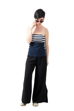 Stern bossy young woman on the mobile phone looking at camera over sunglasses. Full body length portrait isolated over white studio background. Stock Photo