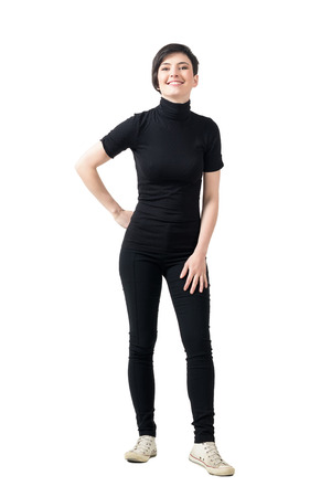 turtleneck: Relaxed young fashionable girl in black turtle neck t-shirt posing and smiling at camera. Full body length portrait isolated over white studio background.