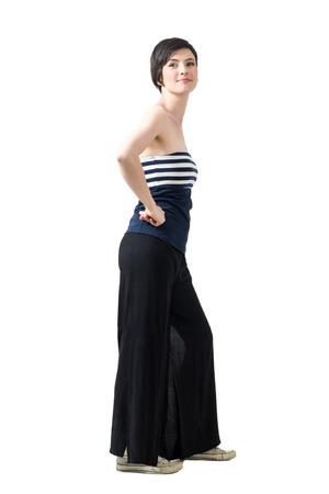 Side view of trendy woman in wide-leg pants and off-the-shoulder top posing at camera. Full body length portrait isolated over white studio background.
