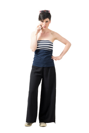 off shoulder: Serious stern woman in wide-leg pants talking on the phone looking at camera. Full body length portrait isolated over white studio background.