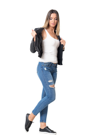 Young casual girl with ombre hairstyle taking off leather jacket. Full body length portrait isolated over studio white background.