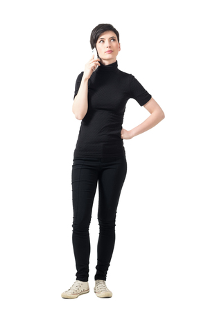 Young elegant woman in black turtleneck talking on the phone looking up. Full body length portrait isolated over white studio background.