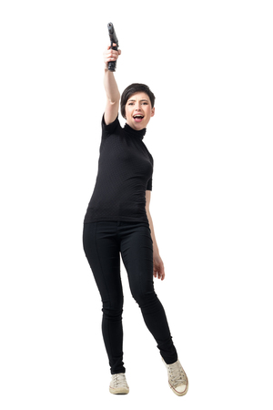 Young female spy in black clothes with gun shooting up in air. Full body length portrait isolated over white studio background.