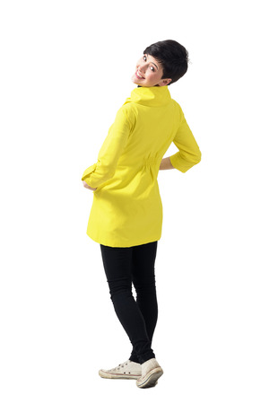 Rear view of young playful woman wearing yellow coat turning and smiling at camera. Full body length portrait isolated over white studio background.